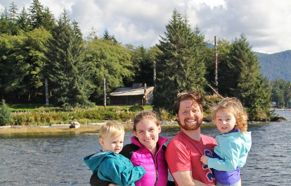 Family of four posing in front of water across the shore from Indigenous Alaskan site