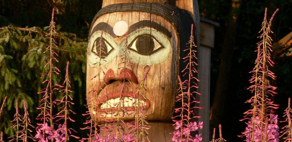 Totem head emerging from flowers