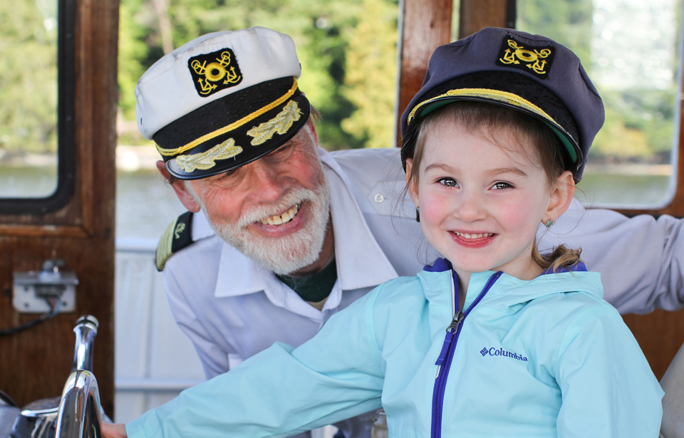 A child and a captain on a boat.