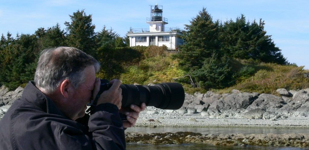 Man taking a photo near Guard Island Lighthouse, AK