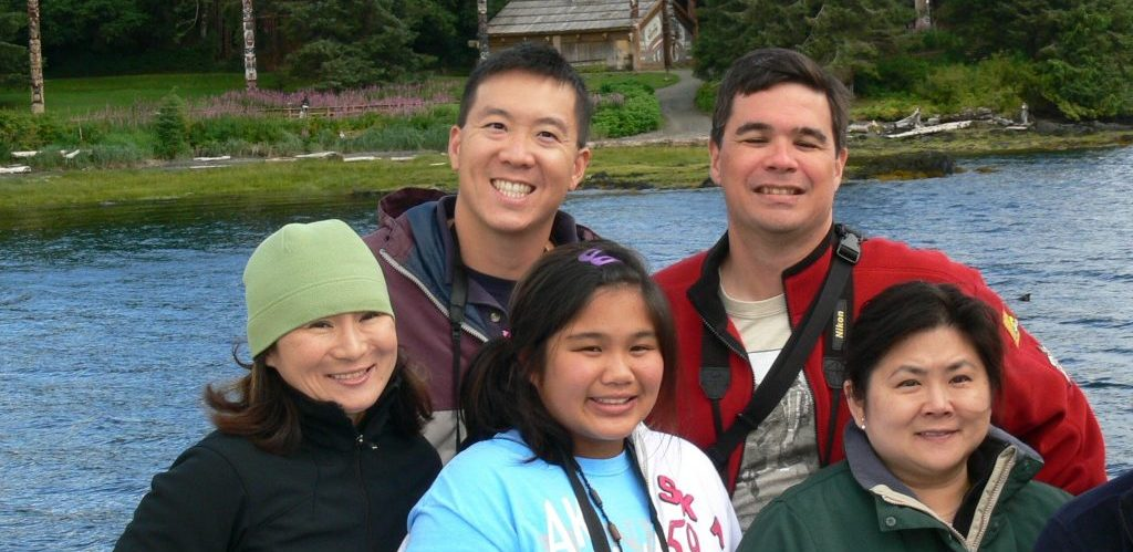 Family smiling at camera, in front of Alaskan Indigenous home